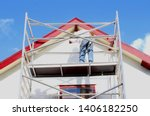 Small photo of Professional workman is painting exterior walls and wooden window frames of ancient house at scaffold tower, outside home renovation in close up under sunny blue sky