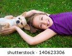 Stock photo children girl playing with chihuahua dog lying on backyard lawn 140623306