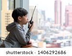 Small photo of Smart looking Asian preteen boy as a young amateur radio operator talking with other ham radio operators reporting radio wave signal strength holding handheld radio in his hand.
