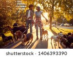 Stock photo girl and man dog walker with dogs enjoying in walk outdoors 1406393390
