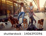 Stock photo smiling girl and man dog walker with group of dogs enjoying in walk 1406393396
