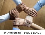 Small photo of Diverse business people team connected grasping hands holding each other wrists in circle, loyalty help in teamwork concept, professional trust power support unity solidarity, close up top view above