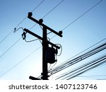 Small photo of Silhouettes of transformers on a pole: convert high voltage energy into low voltage and supply electricity through wires to service recipients. On background blue sky morning.