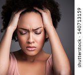 Stock photo young african woman suffering from a terrible headache 140713159
