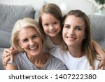 Small photo of Head shot portrait granddaughter mother and grandmother sitting together on sofa at home looking at camera smiling feeling good and satisfied spend free time together. Happy mother day holiday concept