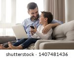 happy young father sit on couch ...   Shutterstock . vector #1407481436