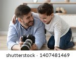 smiling young dad lying on... | Shutterstock . vector #1407481469