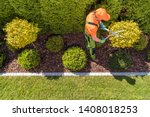 Professional Gardener and the Large Backyard Garden. Top View. Spring Time Maintenance. Trimming Trees and Plants. - stock photo