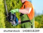 Hedge Trimmer Garden Work. Caucasian Gardener with Trimming Power Tool Closeup Photo.  - stock photo