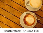 Latte art concept. Two cups with cappuccino (hot coffee with milk foam) and canella (cinnamon) on wooden table at street cafe (coffee bar). Vintage style. Outdoor shot. - stock photo