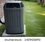Modern air conditioner on backyard with working sprinkler system - stock photo