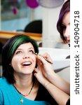 Small photo of Closeup of salon worker applying kajal on woman's eye