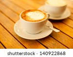 Latte art concept. Two cups with cappuccino (hot coffee with milk foam) and canella (cinnamon) on wooden table at street cafe (coffe bar). Vintage style. Close up. Outdoor shot. - stock photo