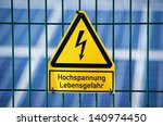 Danger Electrical Hazard High Voltage Sign With Solar Panels in the Background - stock photo