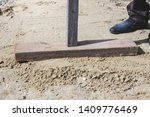 Small photo of Man tamp the sand with a homemade tool, close-up