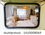 View through the window into the interior of the camper van. Unmade bed, pillows, white wooden interior with lamp center. Cozy sleeping place for a young couple to sleep inside a camper for traveling - stock photo