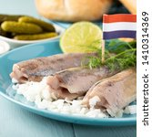 Stock photo traditional dutch food freshly salted herring fish with onion called hollandse nieuwe on turquoise 1410314369