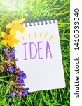 """Small photo of Notepad is lying on the green grass. Summer bright sunny cozy still life. In the notebook, the inscription marker """"Idea"""". The concept of creating original ideas. Next to the notebook - flowers."""