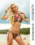Portrait of a beautiful long hair blonde model with great tan posing and standing at the seaside. Bikini fashion. Trendy luxurious accessories (necklace, bracelets). Cloudy weather. Outdoor shot - stock photo