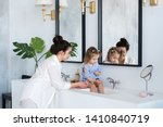 a young woman and a baby wash... | Shutterstock . vector #1410840719