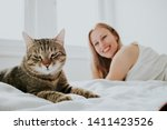 Stock photo blonde woman and cat on white background 1411423526