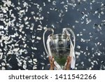 Small photo of KYIV, UKRAINE – MAY 26, 2018: Champions League cup in the hands of the winner, confetti on the background. UEFA Champions League final between Real Madrid and Liverpool. NSC Olympic stadium in Kyiv.