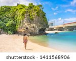 Stock photo young woman in swimsuit from behind on the sandy beach naminoue topped by a huge rock with a shinto 1411568906