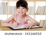 lovely asian girl writing   Shutterstock . vector #141166510
