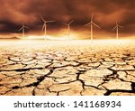 Wind Turbines on a cracked earth desert - stock photo
