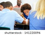 pupils studying at desks in... | Shutterstock . vector #141220096