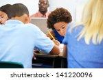 pupils studying at desks in... | Shutterstock . vector #141220096