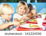 Stock photo elementary pupils enjoying healthy lunch in cafeteria 141224530