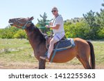 Man Sits Astride A Brown Horse...
