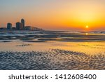 The beach of Ostend city at sunset with unsharp foreground by the North Sea with the urban skyline of sea view apartments, West Flanders, Belgium.