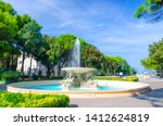 Quattro cavalli Four horses fountain with turquoise water in Parco Federico Fellini park with green trees in touristic city centre Rimini with blue sky background, Emilia-Romagna, Italy
