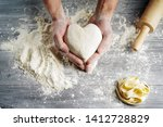 Male hands in flour hold the...