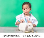 Stock photo asian cute girl wearing white medical uniform with a stethoscope and play examining a baby white 1412756543