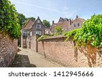Small photo of Middelburg, The Netherlands, May 30, 2019: alley in the old town lined with brick walls that close off private gardens