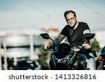 brutal male motorcyclist with glasses sitting on a motorcycle. Motobike driver in the city.