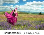Outdoors portrait of a woman in airy crimson dress posing in the blooming field in windy spring day - stock photo