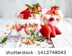 Healthy breakfast of strawberry parfaits made with fresh fruit, yogurt and granola over a rustic white table. Shallow depth of field with selective focus on glass jar in front. Blurred background.
