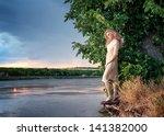 Portrait of a beautiful sad woman on the riverside at sunset - stock photo