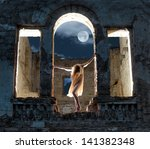 Mysterious female figure standing in the arc of the ruined building in full moon night - stock photo