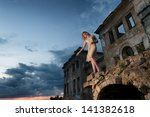Mysterious woman in the ruined building waving to someone - stock photo