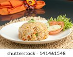 A Thai dish of crab fried rice presented on a square white plate. - stock photo
