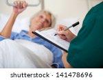 mid adult female nurse writing... | Shutterstock . vector #141478696
