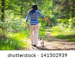Stock photo beautiful brunette on the walk with the dog 141502939