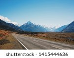 Bitumen road in foreground of snow capped mountain.