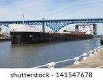 Upbound On The Cuyahoga:  A Great Lakes bulk carrier moves slowly upbound on the Cuyahoga River at Cleveland, Ohio - stock photo