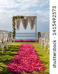 Wedding arch in Boho style near the ocean for a ceremony decorated with macrame and fresh flowers, chairs and pink and red petal aisle. Concept of a tropical wedding. Bali, Indonesia.